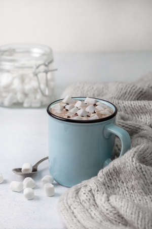 hot chocolate with marshmallows in a blue mug on a light background