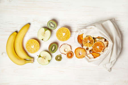 fresh fruits and fruit chips on a white wooden background. view from above