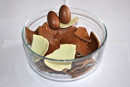 Easter Eggs chocolate. Cracked Eggs chocolate of glass container, white background. Milk and White chocolate Stock Photo