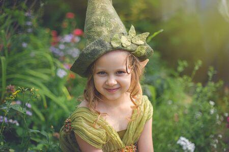 Porträt eines netten hübschen Mädchens in einem Gnomenhut und -kostüm im grünen Wald. Standard-Bild
