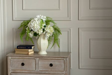A white house with white flowers stands on the dresser against the wall.