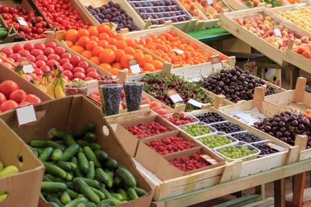 Fresh fruits and vegetables are in trays in the market. 写真素材
