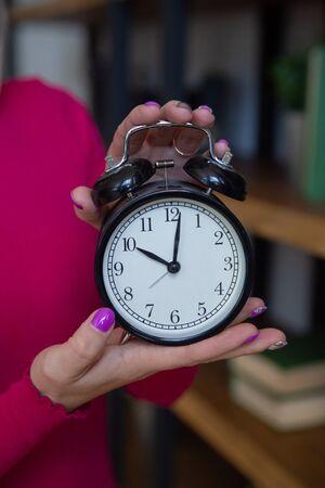Antique alarm clock in the hands of a woman. Banco de Imagens