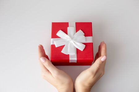 Female hands with red gift box on white background