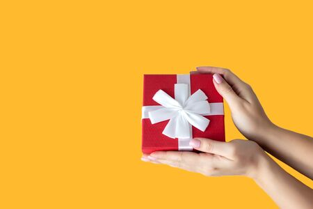 Female hands with red gift box on yellow background Banco de Imagens - 140711644