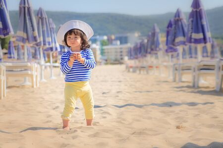 Cute little girl in a blue striped t-shirt, stands on the sand at the beach