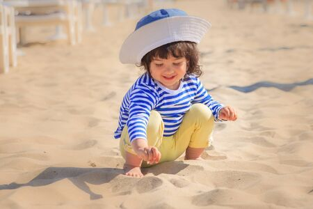 Cute little girl a plays in the sand on the beach
