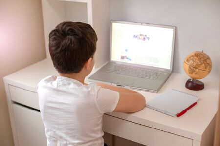 The boy sits with his back behind a laptop, looks at the monitor. Distance learning. Home Study Exam Preparation