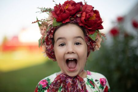 Little funny girl with a red flower crown screams with a big open mouth