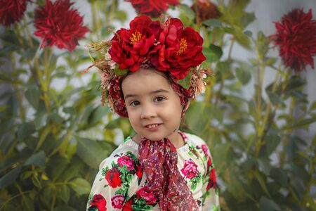 A little girl with a red floral crown sits under a flowering bush with red big flowers Stock Photo
