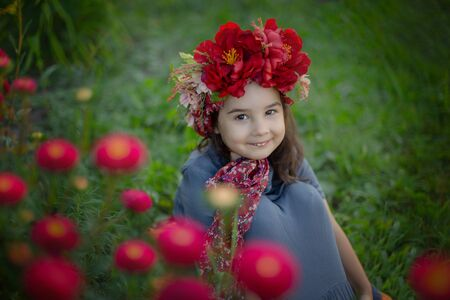 A little girl with a red floral crown sits under a flowering bush with burgundy carnations