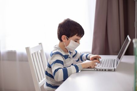 A schoolboy in a white medical mask on his face, sits behind a monitor with a laptop, distance learning .quarantine.