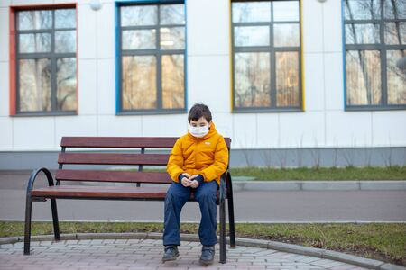 Sad boy in a yellow jacket in a white medical mask sitting on a bench on the street