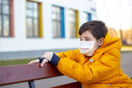 Portrait of a sad boy in a yellow jacket in a white medical mask sitting on a bench on the street Banco de Imagens