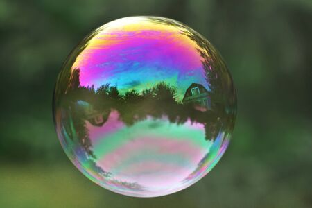 Colorful soap bubble on a green background. Close up