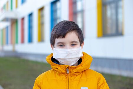 Portrait of a boy in a yellow jacket in a white medical mask on the street