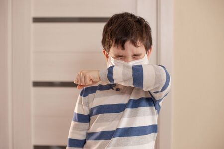 A boy with closed eyes sneezes or coughs into his elbow.