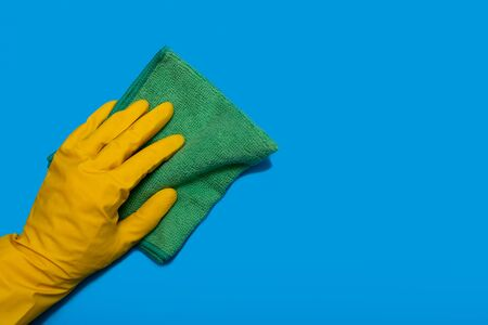 Hand in yellow glove with green rag of microfiber wipes on blue background. Copy space. Horizontal Banco de Imagens