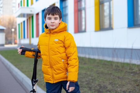 Portrait A boy in a yellow jacket with a scooter stands near the school