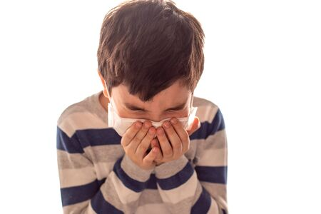 a boy with closed eyes sneezes or coughs in his hands. Influenza