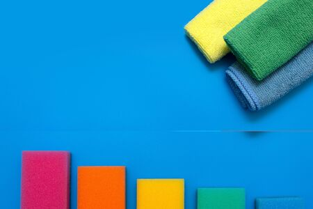 Three colorful, dry microfiber cloths and rainbow colored sponges for cleaning various surfaces in the kitchen, bathroom and other rooms, on a blue background. Copy space .cleaning concept