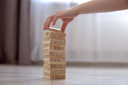 Childrens hand collects a tower of wooden blocks on the floor. Close up. Stay home in quarantine. Family board games