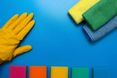 A hand in a yellow rubber glove, three colorful, dry microfiber cloths and rainbow colored sponges for cleaning various surfaces in the kitchen, bathroom and other rooms on a blue background. Copy space .cleaning concept