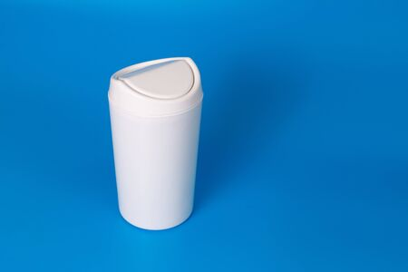 Small table white trash can on a blue background