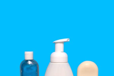 Blue background with a white bottle of liquid soap, a bottle with antibacterial hand gel and a white hand soap Banco de Imagens