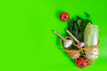 Knitted bag on a green table with vegetables: tomatoes, garlic, potatoes, cabbage, onions and a bunch of dill. Banco de Imagens