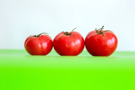 Three large red juicy fresh tomatoes lie on a green table. Close-up. White background.