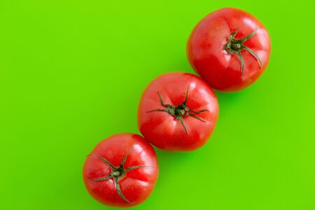 Three large red juicy fresh tomatoes lie on a green table. Close-up. Top view Banco de Imagens