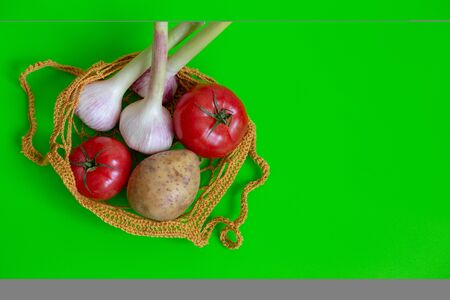 Knitted bag on a green table with vegetables: tomatoes, garlic, potatoes. Vegetarian Vegetables. Healthy Food. View from above. Copy space