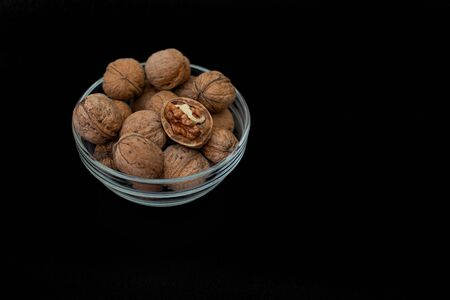 Glass bowl with walnuts in peel on a black background. Copy space.
