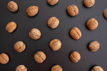Pattern shelled walnuts in a row on black background. Top view.
