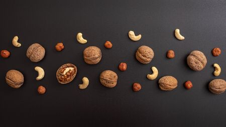Pattern shelled walnut, hazelnut and cashews on black background. Top view. Banco de Imagens