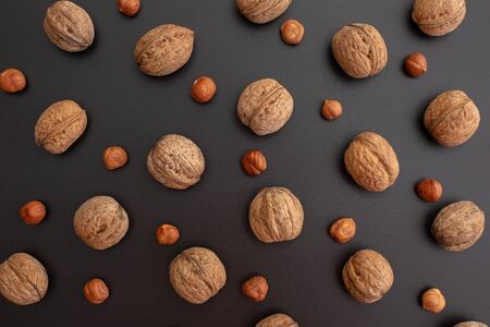 Pattern shelled walnuts and hazelnut in a row on black background. Top view.