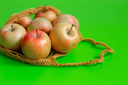 Juicy ripe red-yellow apples lie in a knitted bag on a green background. Copy space