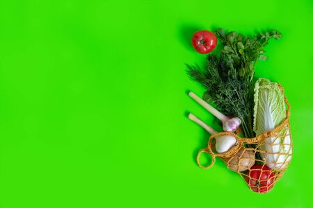 From a knitted bag on a green table, vegetables are scattered: tomatoes, garlic, potatoes, Chinese cabbage, onions and a bunch of dill. Vegetarian Vegetables. Healthy Food. View from above. Copy space Banco de Imagens
