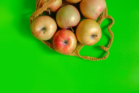 Juicy ripe red-yellow apples lie in a knitted bag on a green background. Top view. Copy space Banco de Imagens