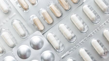 wide background, macro closeup of pills and white capsules, on a silver pharmaceutical blister pack. Close up.
