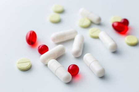 Multi-colored assorted tablets and capsules spilled out of a white table. White background. Copy space Banco de Imagens