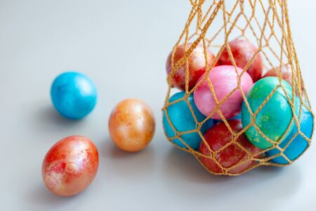 Several ribbed eggs in a knitted bag. Three eggs lie nearby on a white background. Copy space