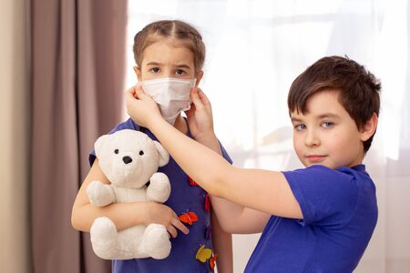 Brother wears a white medical mask to his little sister Banco de Imagens
