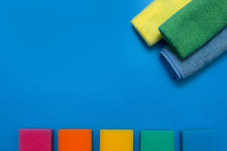 Three colorful, dry microfiber cloths and rainbow colored sponges Archivio Fotografico