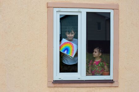 Children from the window show a picture of the rainbow, as a symbol of support during the coronavirus Banco de Imagens