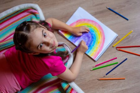 A girl lies on the floor on a striped plaid and draws a rainbow on paper with colored pencils Banco de Imagens