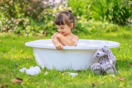 Baby girl bathes in a bathtub in the summer garden Banco de Imagens