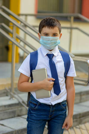 a schoolboy in a white shirt, blue tie and a backpack stands in a medical mask with a tablet