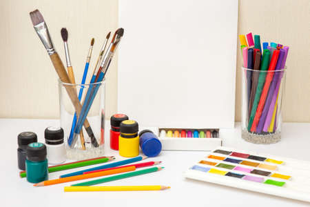 Paintbrushes and colorful drawing supplies on white table. Mock up
